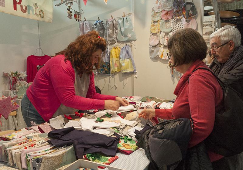 Arancha Sanz, fundadora de Punto y Punto, marca textil artesana aragonesa, atiende a unos clientes en el mercado de artesanía del Auditorio de Zaragoza (diciembre 2017)